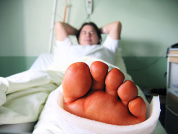 man in hospital bed with cast